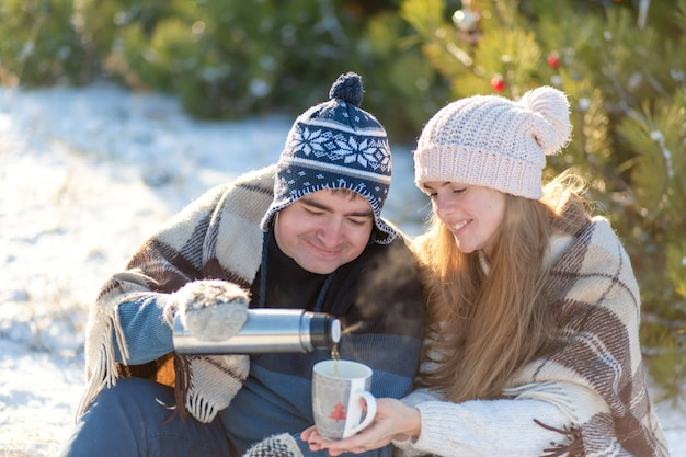Young couple in love drink a hot drink from a thermos,