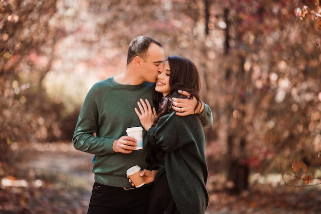 Young couple in love drinking coffee on a walk in the autumn forest