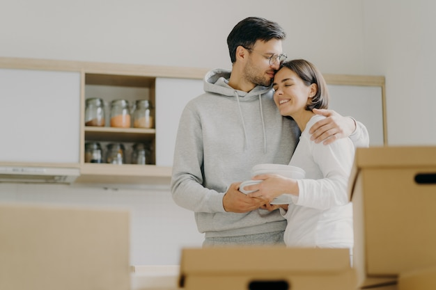 Young couple in love embrace and kiss with tender, hold pile of white plates, stand in kitchen during moving day, surrounded with many carton boxes filled with personal belongings, unpack stuff