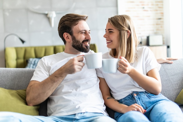 Young couple in love enjoying their free time, sitting on a couch, drinking coffee