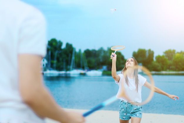 Young couple in love female girl and man male teenagers adults playing in badminton