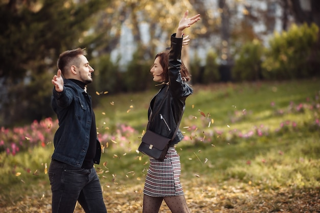 Young couple in love fooling around tossing fallen leaves up in autumn park