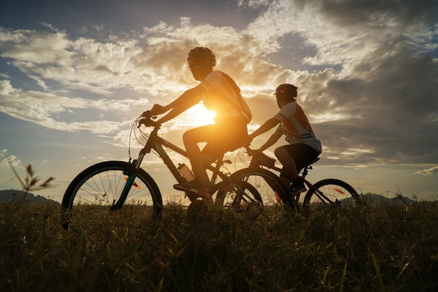 Young couple in love fun and happy riding mountain bike after covid-19 coronavirus outbreak. end of the coronavirus outbreak. silhouette cycling man and woman riding mountain bike at sunset time.