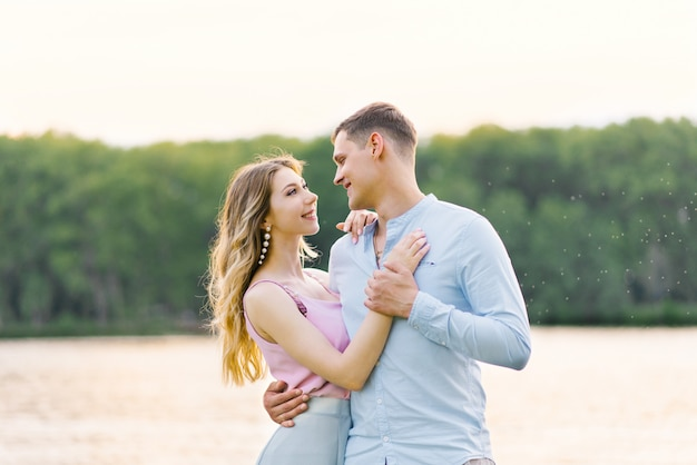 Young couple in love: guy and girl look on each other