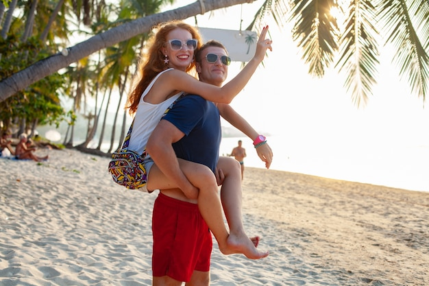Giovani coppie nell'amore felice sulla spiaggia di estate insieme divertendosi