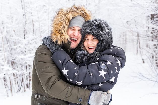 Young couple in love have fun in the snowy forest. active winter holidays.