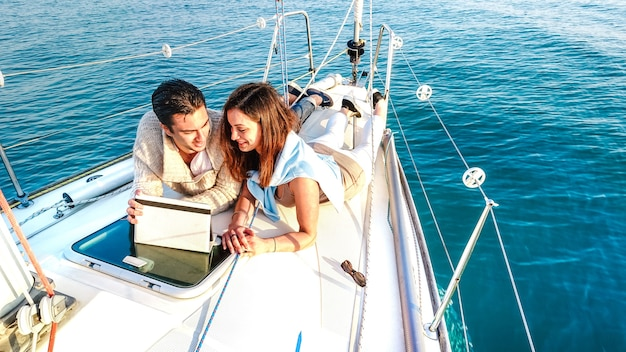 Young couple in love having fun with tablet pc on sailboat - luxury travel life style and digital nomad concept on exclusive yacht tour - bright vivid filter with soft fisheye lens distortion