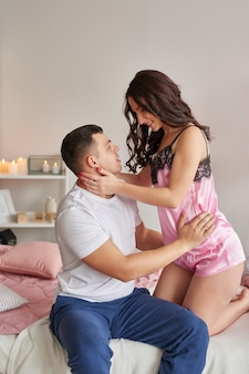 Young couple in love at home on bed celebrating valentine's day