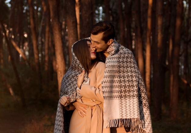 Young couple in love hugging and kissing covered in blanket in autumn forest. happy man and woman having romantic date