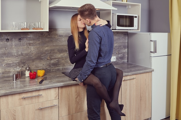 Young couple in love kisses of kitchen.