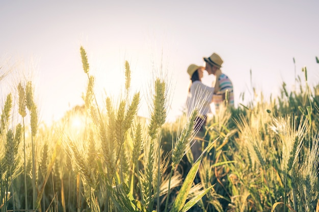 Young couple in love kissing on a wheal field
