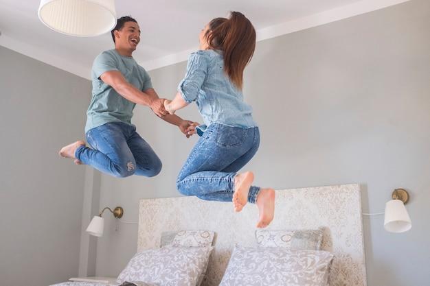 若いカップルは家で一緒に生活を愛し、寝室で空中にジャンプします-ミレニアル世代の男の子と女の子が楽しんで、ベッドの上でたくさん笑っている新しい家の購入のコンセプト