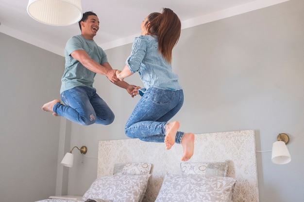 Young couple love life together at home and jump in the air in the bedroom - new house buy concept with millennial boy and girl having fun and laughing a lot jumping on bed