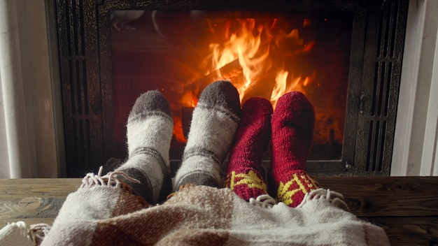 Young couple in love lying under blanket by the fireplace