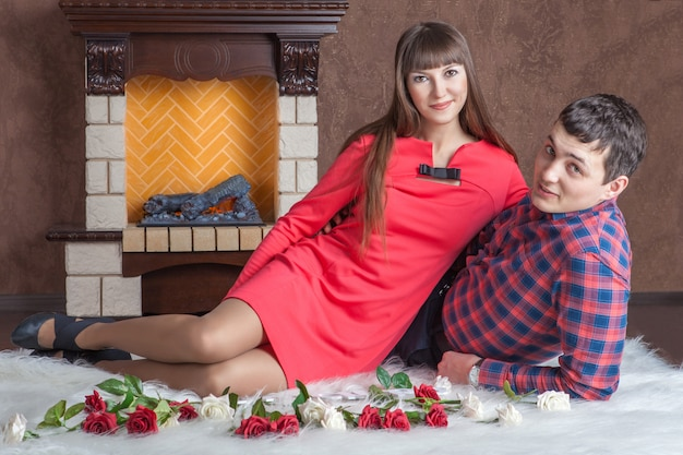 Young couple in love lying near the fireplace on carpet.