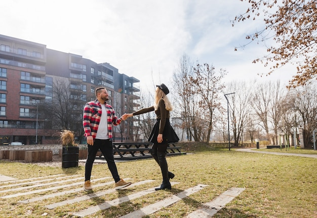 Young couple in love outdoor. cute couple of young hipster people walking in spring old town on weekend vacation. happy guy and girl. travel.