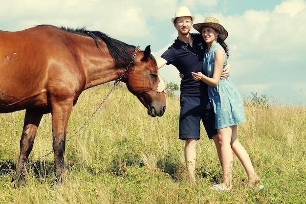 Young couple in love outdoor.stunning sensual outdoor portrait of young couple posing in summer sunset near horse.