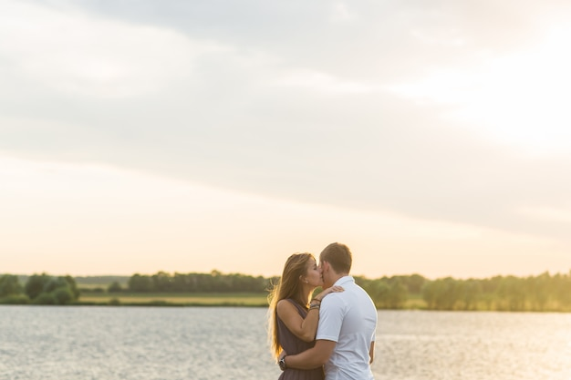 Young couple in love outdoors embracing and laughing together at lake.