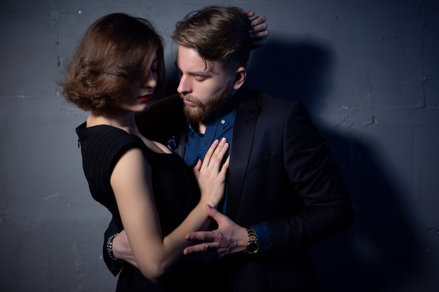 A young couple in love passionately embraces in a room with low lighting.