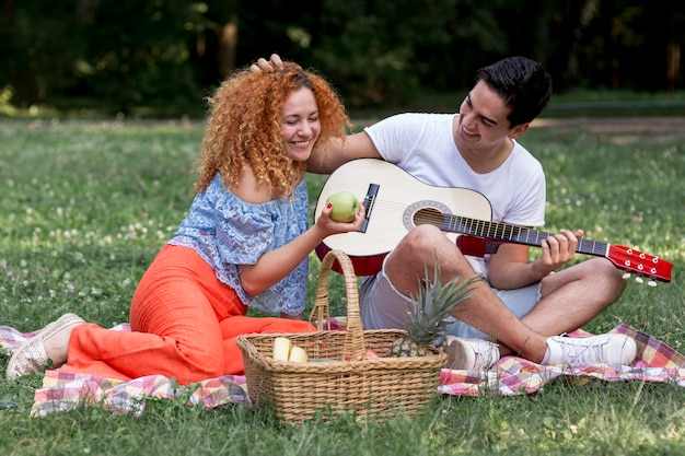 Young couple in love on picnic blanket