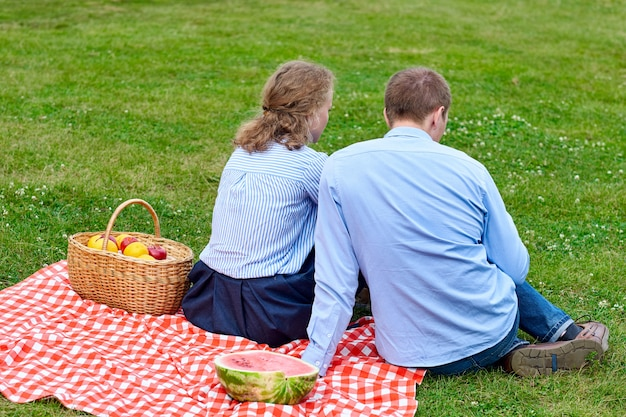 Young couple in love on picnic sitting on tablecloth in red cell. love couple resting in nature in meadow or park