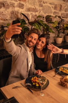 Young couple in love in a restaurant, having fun dining together, celebrating valentine's day, taking a souvenir selfie. vertical photo