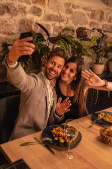 A young couple in love in a restaurant, having fun dining together, celebrating valentine's day, taking a souvenir selfie
