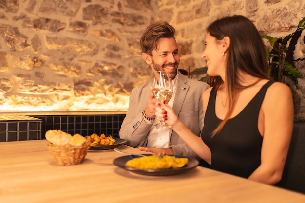Young couple in love in a restaurant, toast the glasses of wine, celebrating valentine's
