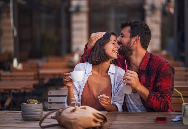 Young couple in love sitting in a cafe and have fun