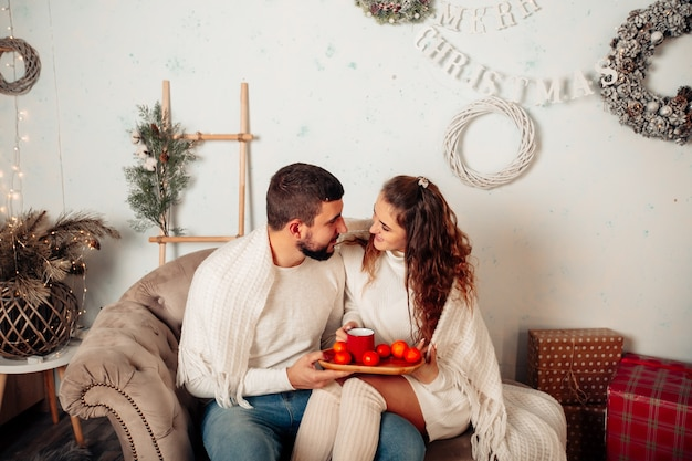 Young couple in love sitting on sofa and kissing while holding a cup of tea in christmas setting