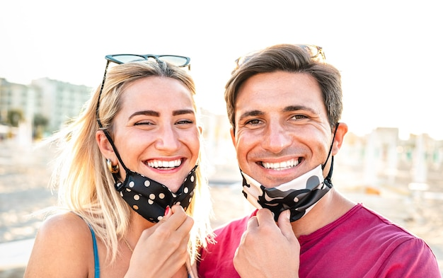 Young couple in love smiling with open face mask