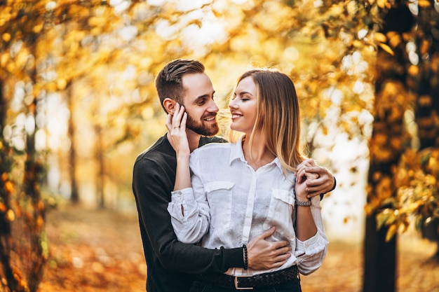 A young couple in love walking in the autumn park on a sunny day