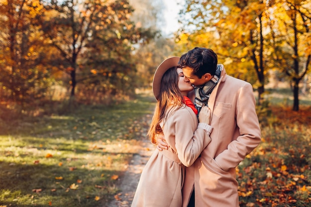 Young couple in love walks in autumn forest among colorful trees. stylish people hugging and kissing at sunset