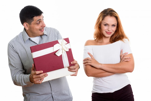 Young couple in love with man looking at woman while opening gift box looking surprised