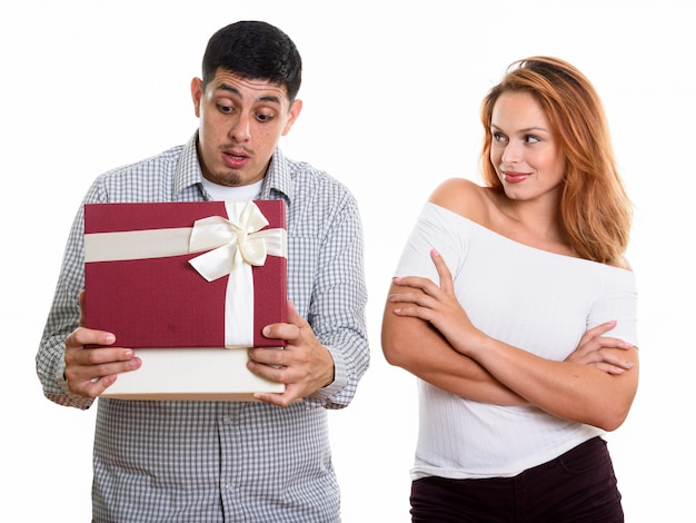 Young couple in love with man opening gift box looking surprised