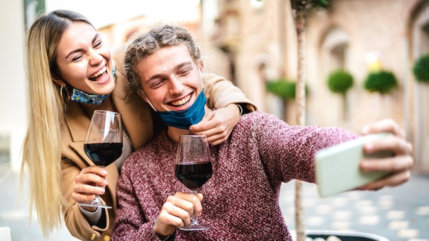 Young couple in love with open face mask taking selfie at outside wine bar