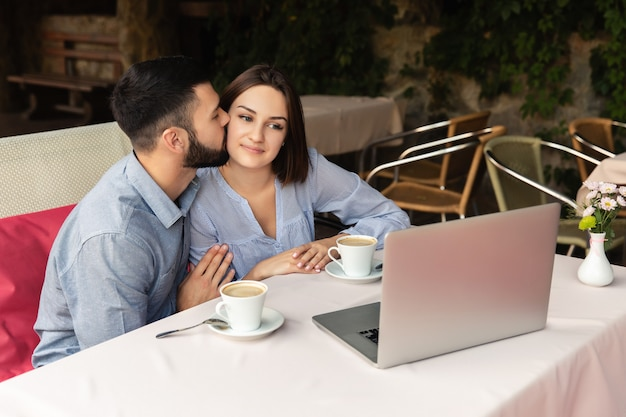 Young couple in love working from home, man kisses woman on the cheek, and she looks at the laptop indoors