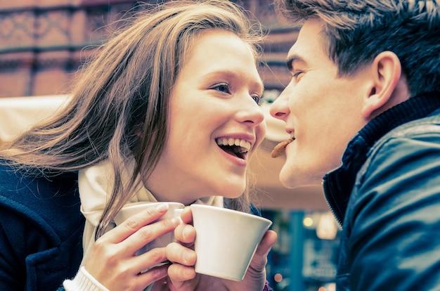 一杯のコーヒーを楽しんで素敵な若いカップル