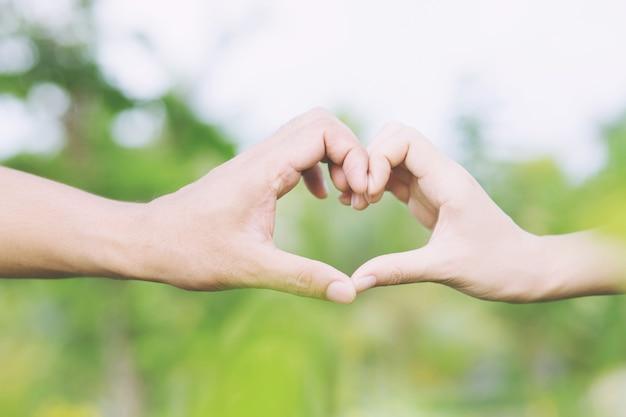 손을 잡고 젊은 부부 연인 쇼는 공공 공원에서 심장 모양을 만듭니다.