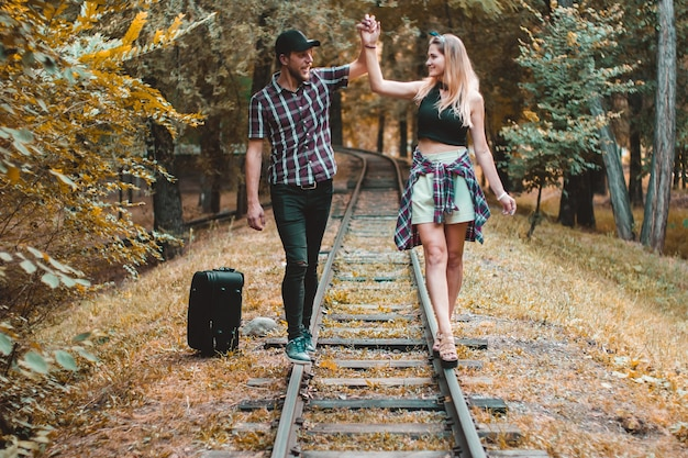 A young couple of lovers missed the train. walking on the rails in the autumn forest waiting for the next train.