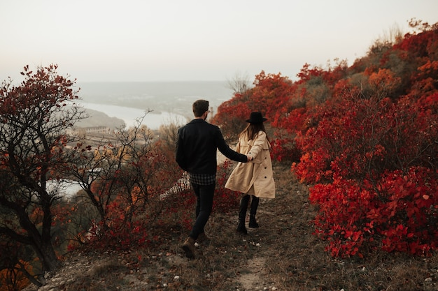 A young couple of lovers walking holding hands against of red autumn leaves
