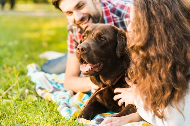 Young couple loving their dog in garden