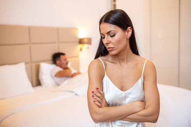 Young couple lying in bed under blanket in bedroom at home