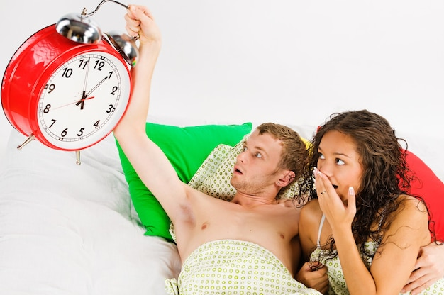 Young couple lying in bed and checking big alarm clock