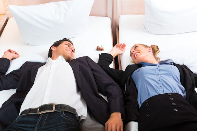 Young couple lying on bed in hotel room