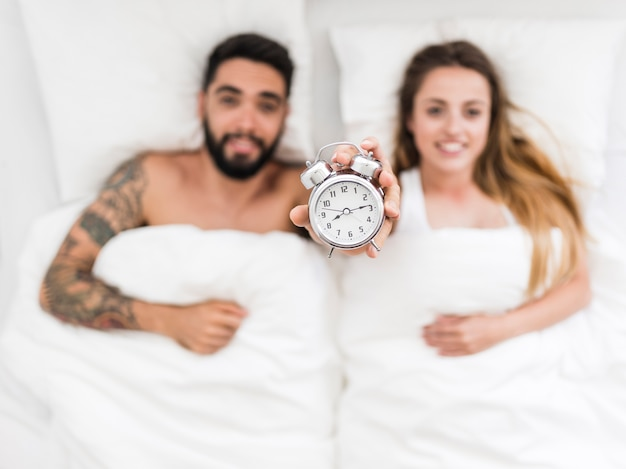 Young couple lying on bed showing alarm clock