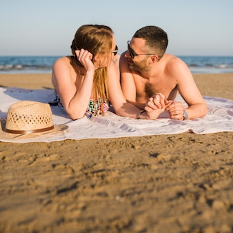 Young couple lying on blanket near the seashore looking at each other at beach