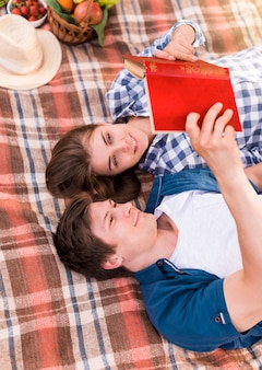 Young couple lying on blanket and reading book