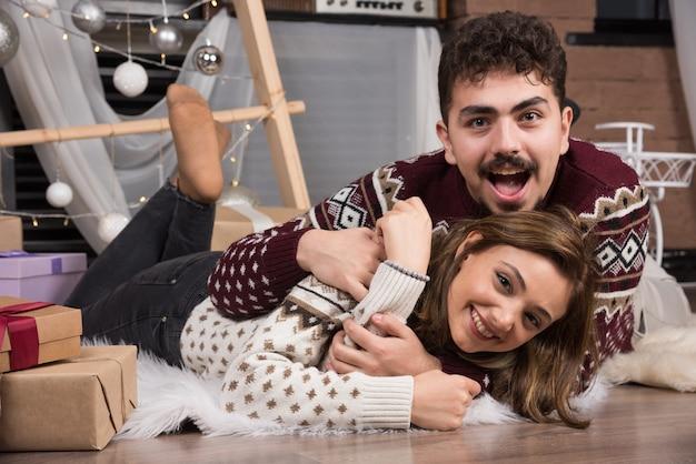 クリスマスのインテリアの床に横になっている若いカップル。
