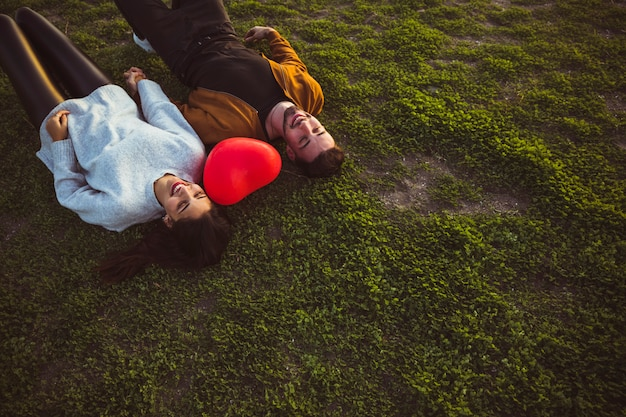 Young couple lying on grass with red heart balloon